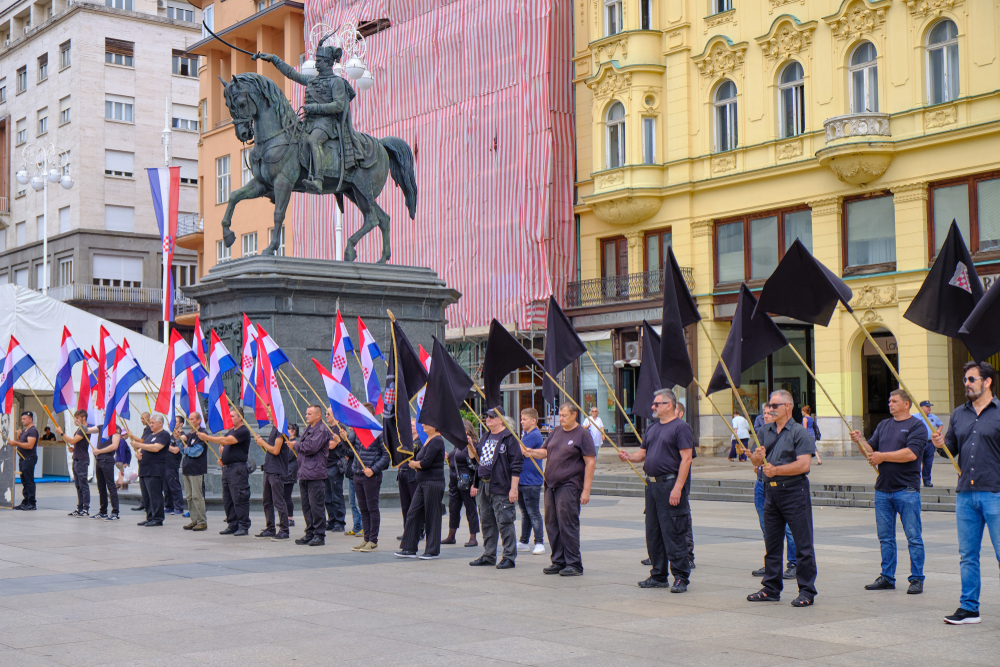 Zagreb, Croatia, June 23, 2019 : Right wing political rally in city main square, featuring man dressed in black waving Croatian, Black and Anti EU flags (© meandering images/Shutterstock)