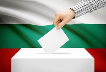 Elettore inserisce la scheda nell'urna sullo sfondo di una bandiera bulgara - © Niyazz/Shutterstock