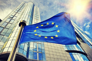 Bandiera dell'UE sventola davanti alla sede del Parlamento europeo a Bruxelles © symbiot/Shutterstock