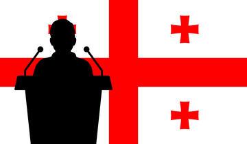 Siloutte nera di uno speaker, sullo sfondo la bandiera georgiana (© Stock Ninja Studio/Shutterstock)