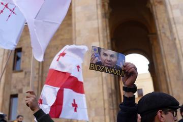Un manifestante regge un cartello con la scritta in russo 'Fottiti Bidzina' all'esterno del parlamento georgiano la scorsa domenica (Mari Nikuradze/OC Media)