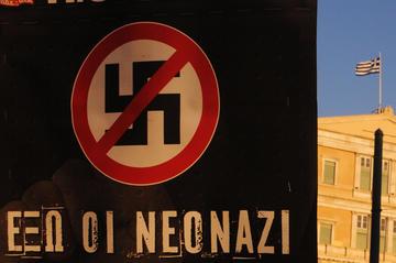 """Un cartello con una svastica e il segno di divieto, con scritto """"Via i nuovi nazi""""(© Kostas Koutsaftikis/Shutterstock)"""