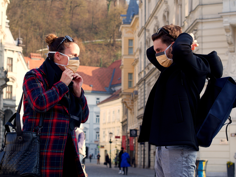Young couple putting on a face protection face mask in the city center of Ljubiana - © Gasper Grubelnik/Shutterstock
