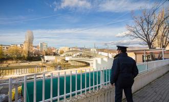 Un poliziotto osserva il ponte sul fiume Ibar che separa la città di Mitrovica nella parte serba e albanese © BalkansCat/Shutterstock