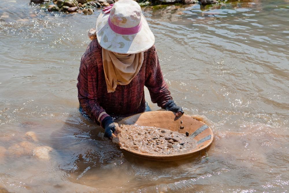 زن ماسه رودخانه را برای طلا می مالد (عکس © Muellek Josef / Shutterstock)