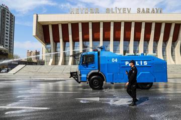 Un camion e un spruzza del disinfettante per le strade di Baku, per limitare il contagio da Covid19