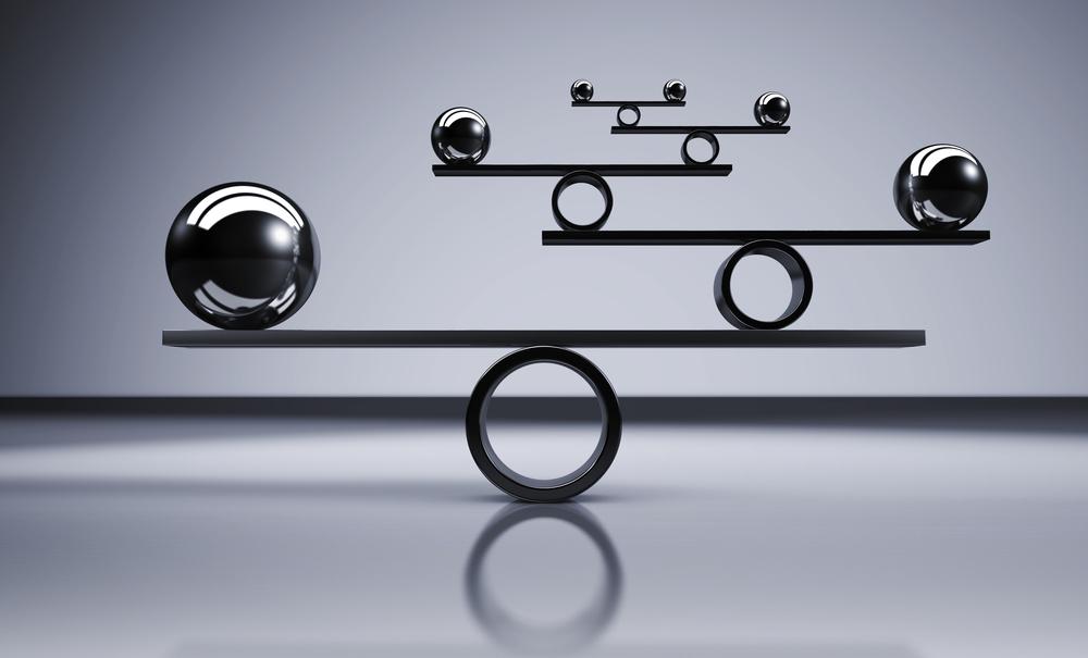 Sfere di metallo bilanciate su sfondo grigio, illustrazione 3D © niroworld/Shutterstock