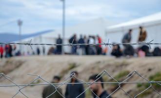 Migranti dietro il filo spinato di un campo © Ajdin Kamber/Shutterstock
