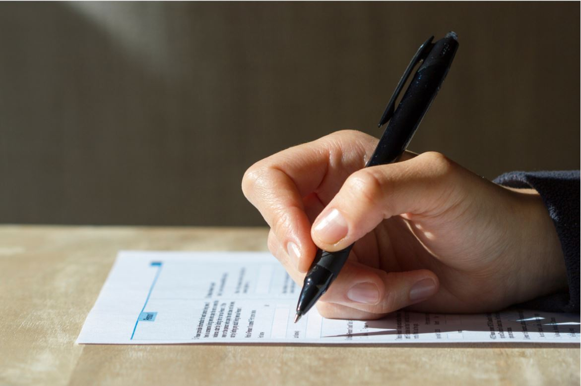 Closeup of woman's hand holding a pen filling out a census form - © Tada Images/Shutterstock