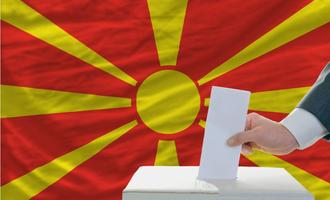 Man putting a ballot in a box during elections in North Macedonia in front of the state's flag -  © vepar5/Shutterstock