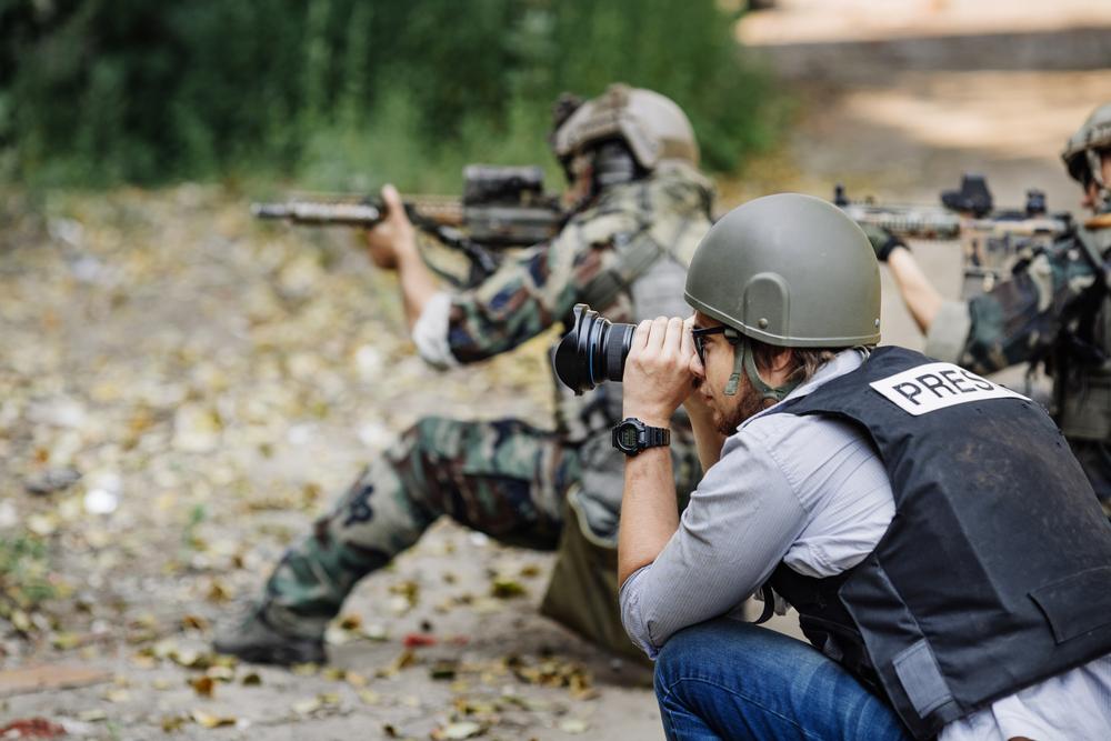 Un reporter fotografa una scena di guerra insieme con dei militari © PRESSLAB/Shutterstock