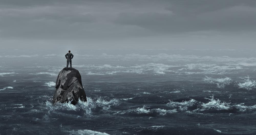 Un uomo solo sta in pidi su uno scoglio nel bel mezzo di un mare in burrasca © Lightspring/Shutterstock