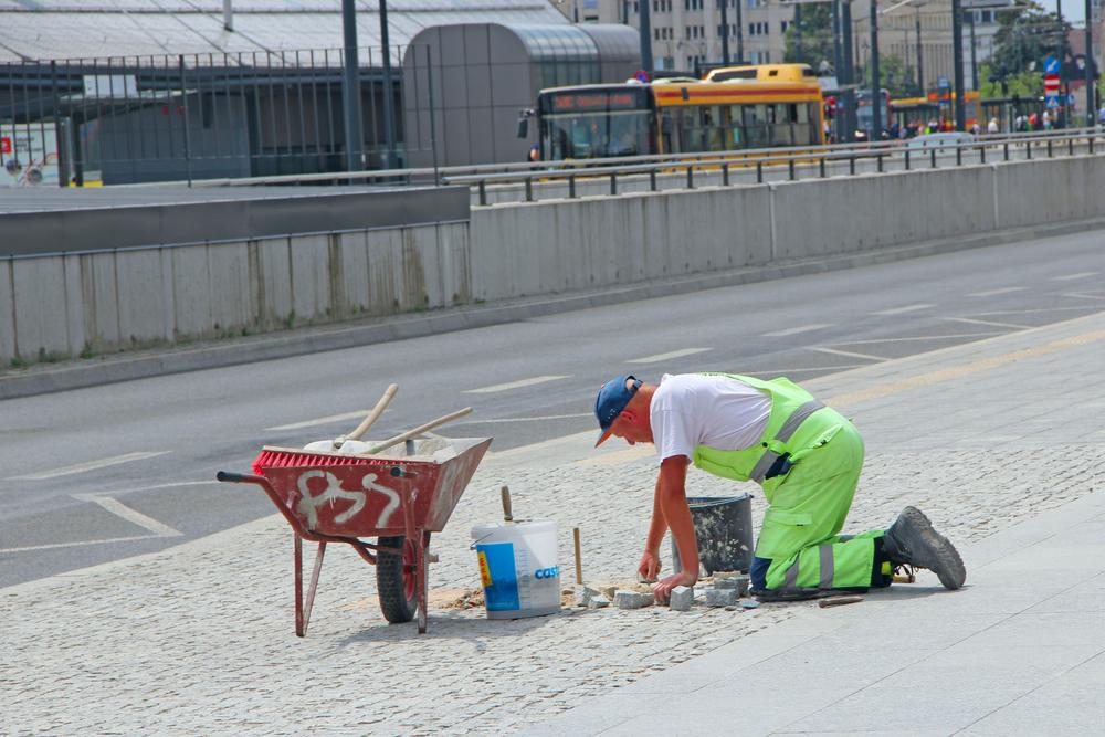 Un lavoratore intento a riparare un marciapiede in Polonia (© alexmak7/Shutterstock)