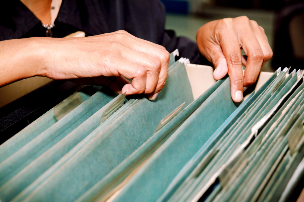 Mani di donna che cerca in un vecchio archivio © chalermphon_tiam/Shutterstock