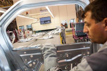 Un uomo rtasporta una portiera nella fabbrica della Dacia-Renault a Mioveni, Romania (punghi/Shutterstock)
