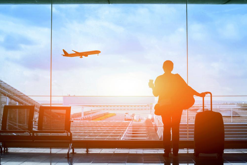 Viaggiatrice all'aeroporto guarda fuori dalla finestra © Song_about_summer/Shutterstock