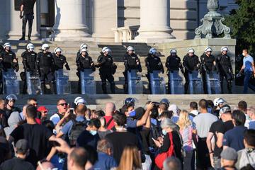 Gruppo di persone protesta davanti ad un cordone di polizia in tenuta antisommossa (© Bobica10/Shutterstock)