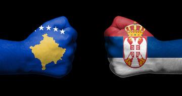 Due mani a pugno una contro l'altra colorate rispettivamente con la bandiera kosovara e quella serba