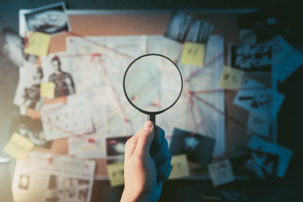 Detective mano che tiene una lente di ingrandimento di fronte a una tavola con prove, foto della scena del crimine e mappa (© Fer Gregory/Shutterstock)
