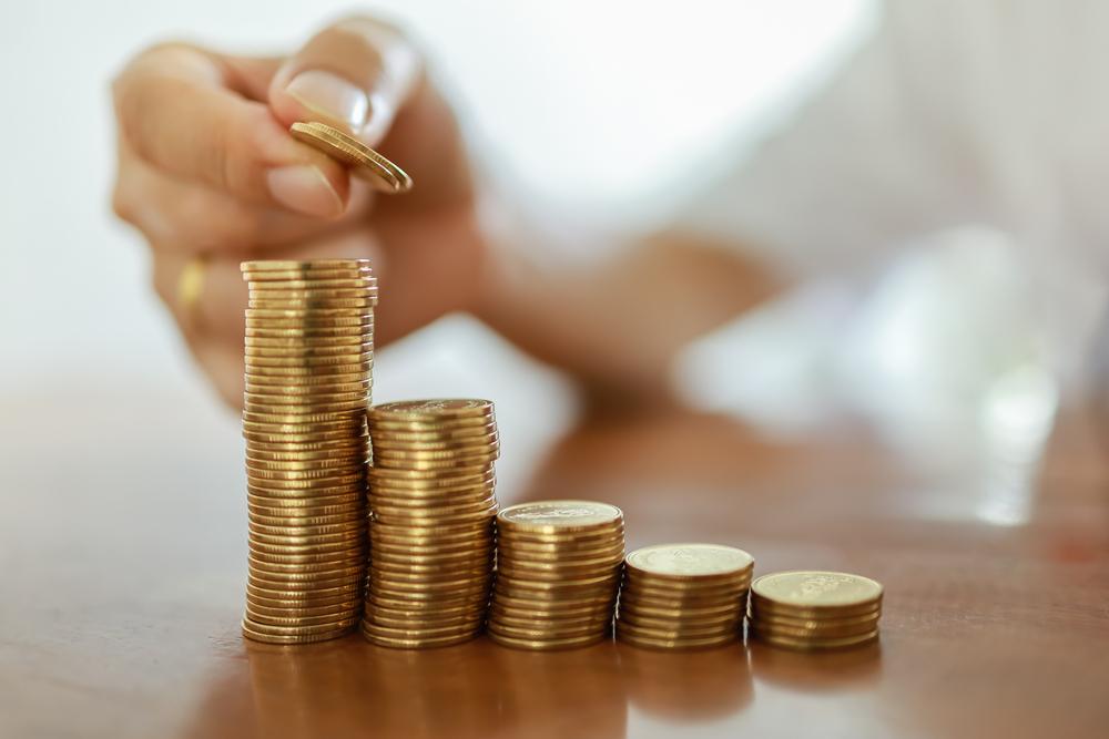 Una mano impila delle monete di metallo (© Montri Thipsorn/Shutterstock)