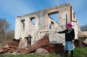A resident of Ergneti on the South Ossetia ABL shows damage inflicted on her house during the conflict © Onnik Krikorian