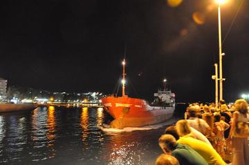 La folla assiste al passaggio di una nave dal ponte 'retrattile' sull'Euripo