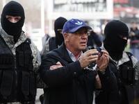 L'arresto di Ramkoski davanti alle telecamere, circondato da agenti a volto coperto (frame dal notiziario Ap)