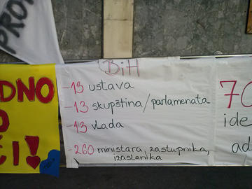 "Un cartello nella manifestazione di ieri a Tuzla recita: ""Bosnia-Erzegovina: 13 costituzioni, 13 parlamenti, 13 governi, 260 fra ministri e parlamentari"""