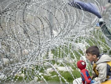 Un bambino gioca vicino alla rete che separa Grecia e Macedonia a Idomeni, 7 marzo 2016 (Foto Jordi Bernabeu Farrús, Flickr)