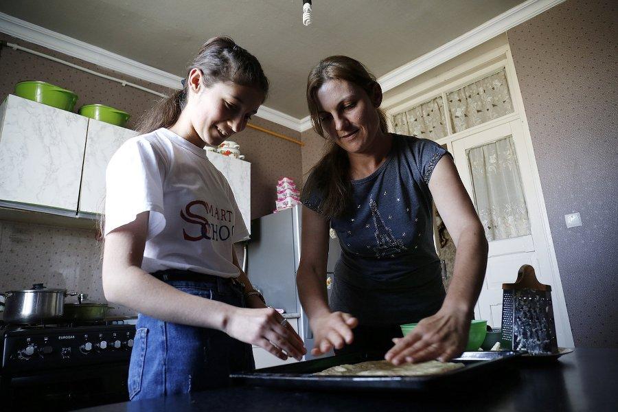 """Zina e sua madre preparano un piatto georgiano tradizionale, il khachapuri, una focaccia ripiena di formaggio. Anche lo zio di Zina trascorre metà dell'anno lavorando in Russia. """"Durante quei mesi il peso della casa cade sulle spalle di tre donne: mia madre, mia nonna e mia zia Roza."""""""