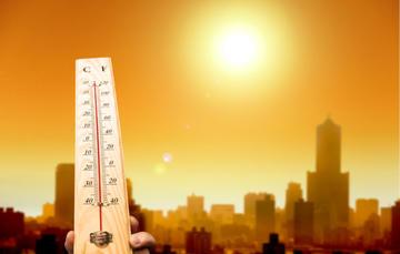 Termometro in primo piano, sullo sfondo grattacieli al tramonto