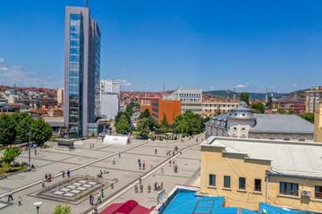Vista dall'alto della piazza Scanderbeg di Pristina, con un grattacielo sulla sinistra, la nuova fontana al centro e all'orizzonte le case sulle colline