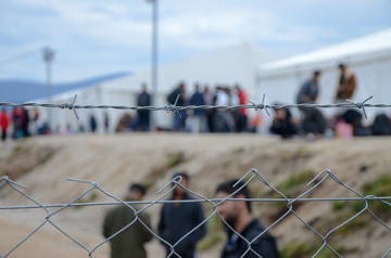 Migrants behind barbed wire in a camp © Ajdin Kamber/Shutterstock