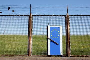 Installazione artistica raffigurante una rete col filo spinato e una porta sbarrata con la bandiera Ue (© Hieronymus Ukkel/Shutterstock)